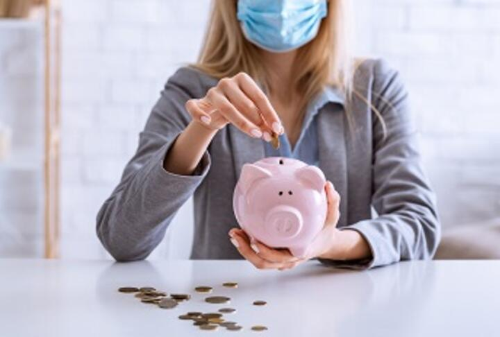 Business woman with mask puts money into piggy bank