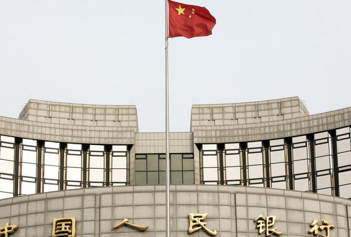 "A Chinese flag flies in front of the People's Bank of China headquarters in Beijing, China. On Monday, the central bank said it is ""almost ready"" to release a digital currency that has been five years in development. Giulia Marchi—Bloomberg via Getty Images"