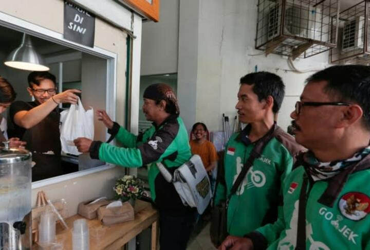 Go-Jek drivers wait for orders at a coffee stall in Jakarta- The app has become much more than a ride hailer -Credit Reuters