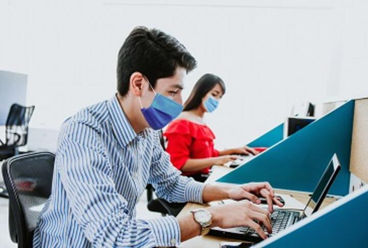 A young male and female with masks working with computers