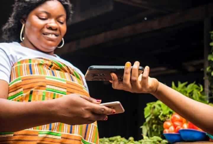 African lady selling in a local market receiving payment via contactless transfer of funds from a customer using their mobile phones