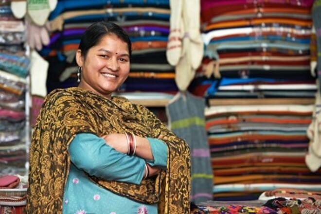 Indian woman smiling in front of a clothing store