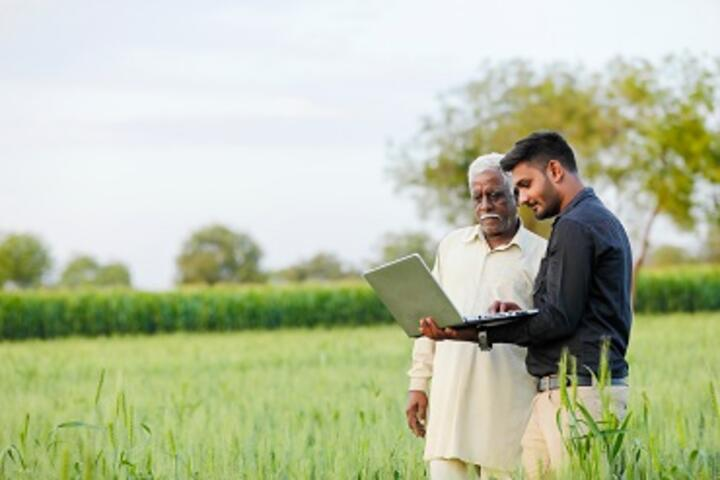 Old man and young man with computer on a crop field