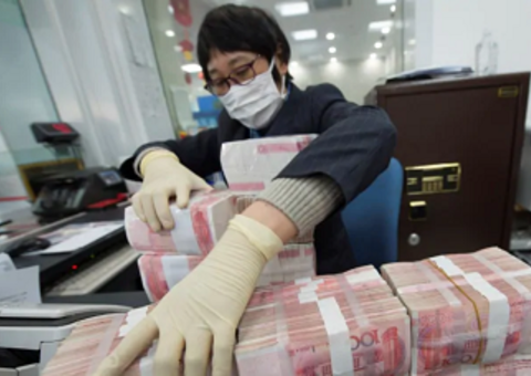 A bank employee wearing a mask arranges stacks of Chinese yuan notes at a bank in Nantong, Jiangsu province, China on Jan 30, 2020.PHOTO: REUTERS