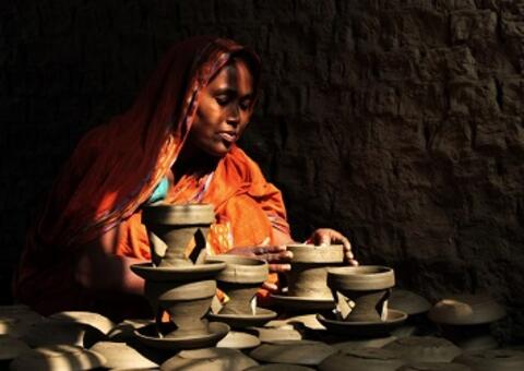 An entrepreneur in Bangladesh puts the finishing touches on her clay pots. Photo: Moksumul Haque, 2015 CGAP Photo Contest
